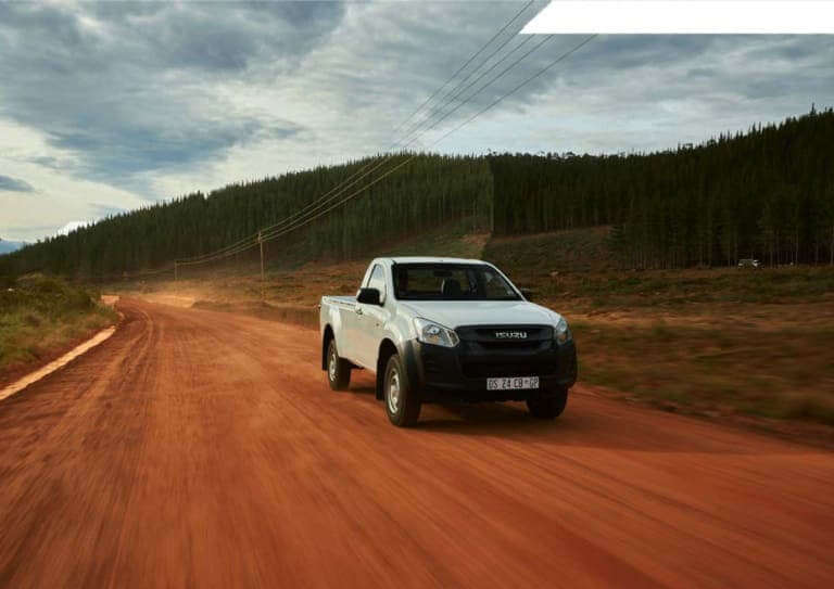 Isuzu  White KB Bakkie Driving On Dirt Road